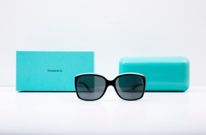 A pair of black Tiffany sunglasses are displayed in front of the iconic turquoise blue Tiffany box and sunglasses case.