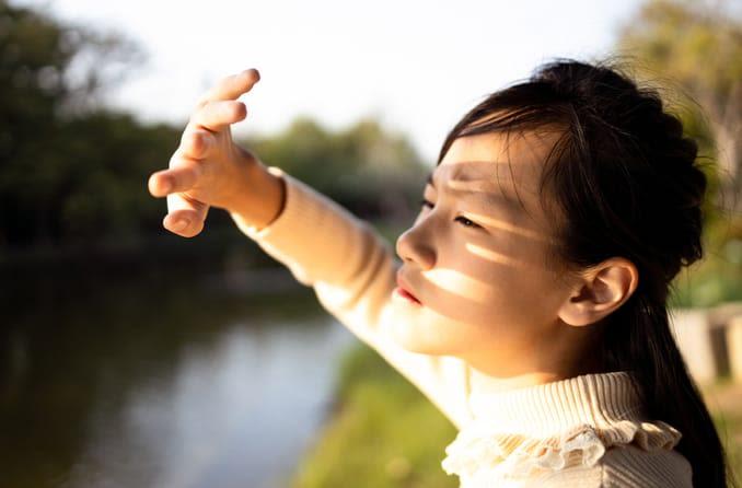 Garota asiática tapando o sol do rosto com as mãos por causa da fotofobia