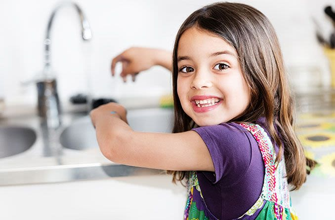 Little girl washing her hands and smiling