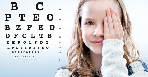 Girl covers one eye and looks at eye chart