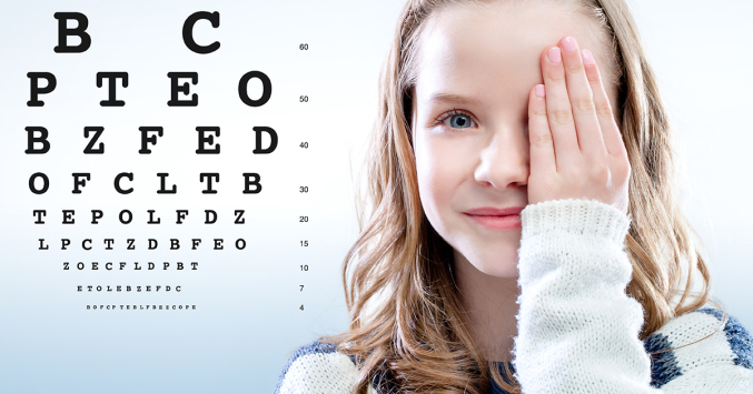 girls covers one eye and looks at eye chart