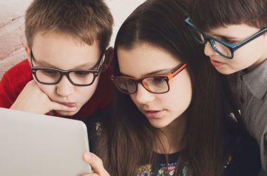 Three children wearing glasses looking at computer screen