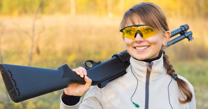 woman wearing shooting glasses and holding gun