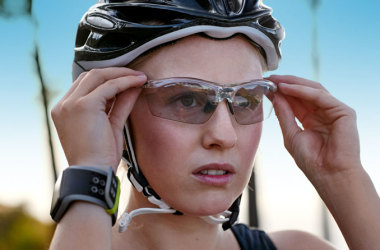 female bicycler puts on protective eyewear