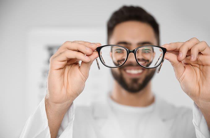 oculista sosteniendo un par de anteojos