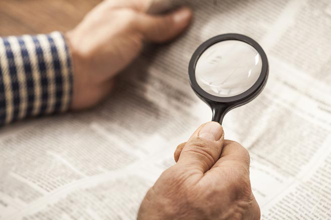 Magnifier glass used to read newspaper