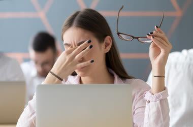 Mujer con fatiga visual por el uso prolongado de la computadora