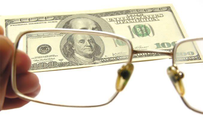 $100 dollar bill seen through eyeglass lenses
