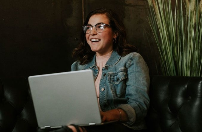 Happy woman with eyeglasses on her laptop - FSA