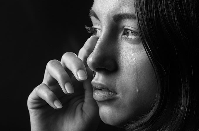 woman wiping her tears away from her eye