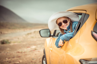 Girl in hat and sunglasses looking out car window