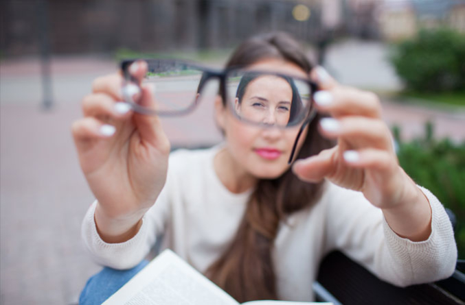 Woman looking at a pair of eyeglasses