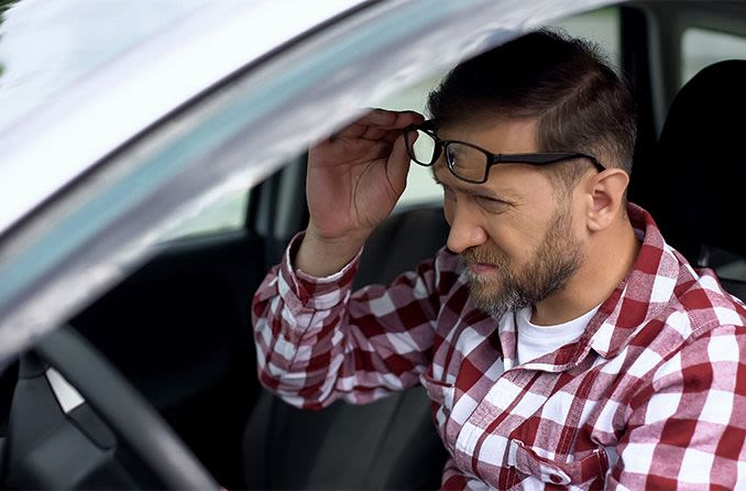 Man having trouble seeing lifting up his eyeglasses while driving