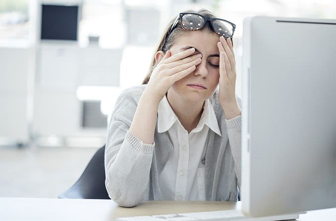 woman a computer rubbing tired eyes