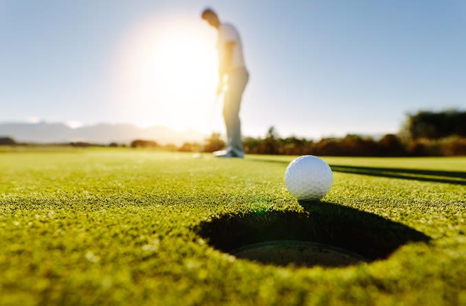 A man wearing sunglasses plays golf.