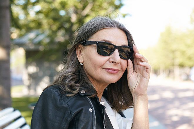 Mature woman wearing wayfarer sunglasses outdoors