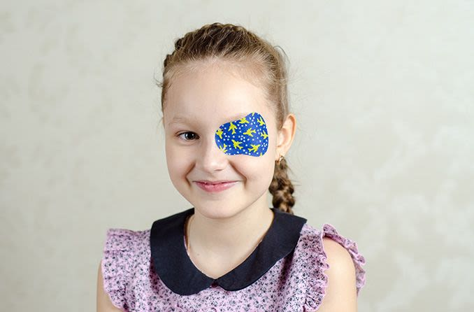 young girl with a lazy eye wearing an eye patch at home for treatment