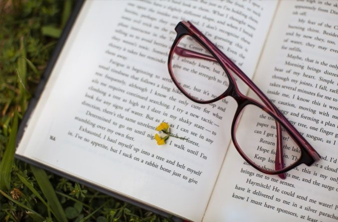 A pair of eyeglasses on top of an open book
