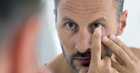 Un hombre que pone sus lentes de contacto en sus ojos.
