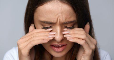 kadının yanma hissi nedeniyle gözleri üzerinde parmakları var