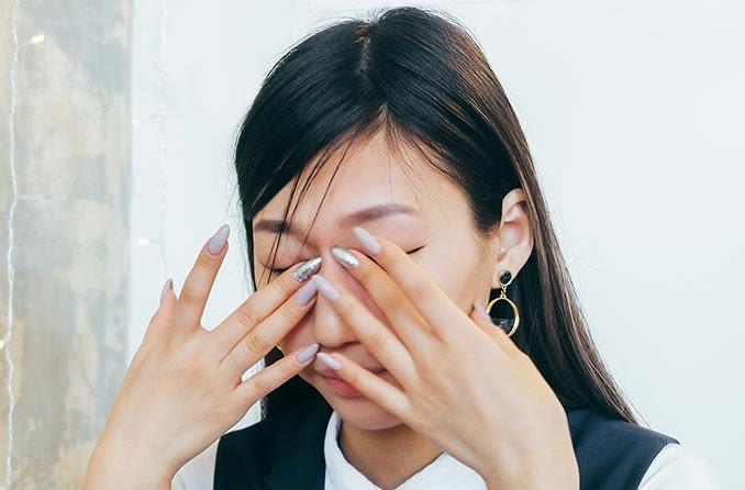 灼熱感のために女性が目の上に指を持っている