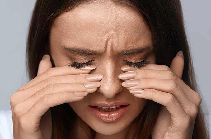 المرأة لديها أصابع على عينيه بسبب حرقان
