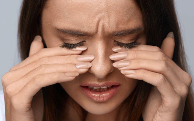 La femme a les doigts sur les yeux en raison d'une sensation de brûlure