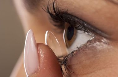 Woman placing contact lens on eye