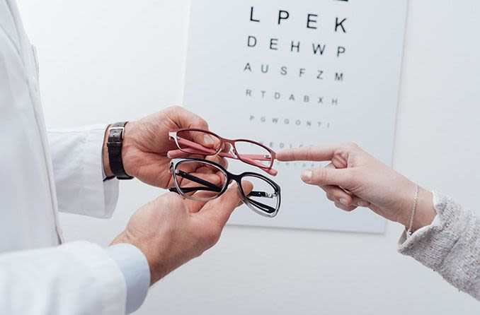 Eye chart in background with person choosing pair of eyeglasses from an optometrist
