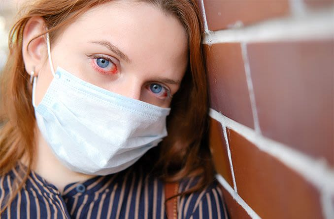 woman wearing a surgical mask who has coronavirus red eyes