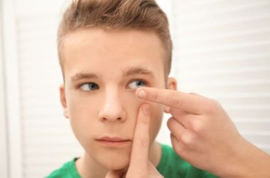 Teen boy inserting contact into eye