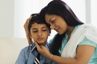 एक युवा भारतीय लड़के को उसकी माँ ने दिलासा दिया है।