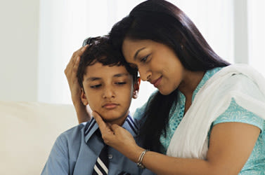 A young Indian boy is comforted by his mother. - India