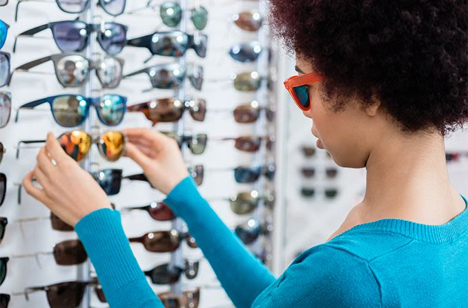 woman choosing between plastic or glass sunglass lenses