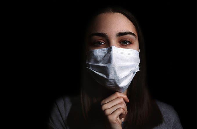 Donna che indossa una maschera per prevenire la diffusione del virus