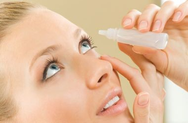 Woman using eye drops to aid Lasik recovery.