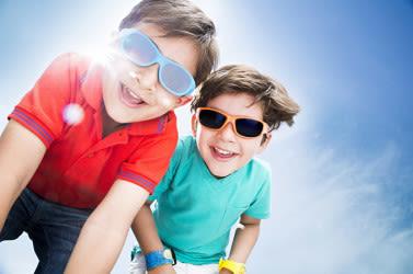 छोटे बच्चे धूप का चश्मा पहने बाहर।