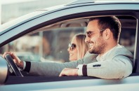 Happy couple driving in a car wearing sunglasses