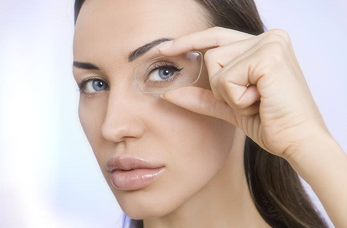 woman holding up an eyeglass lens to her eye