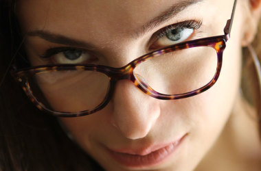 woman wearing spectacles looking up