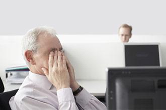 Trabajador de oficina frotándose los ojos mientras está sentado delante de la computadora.