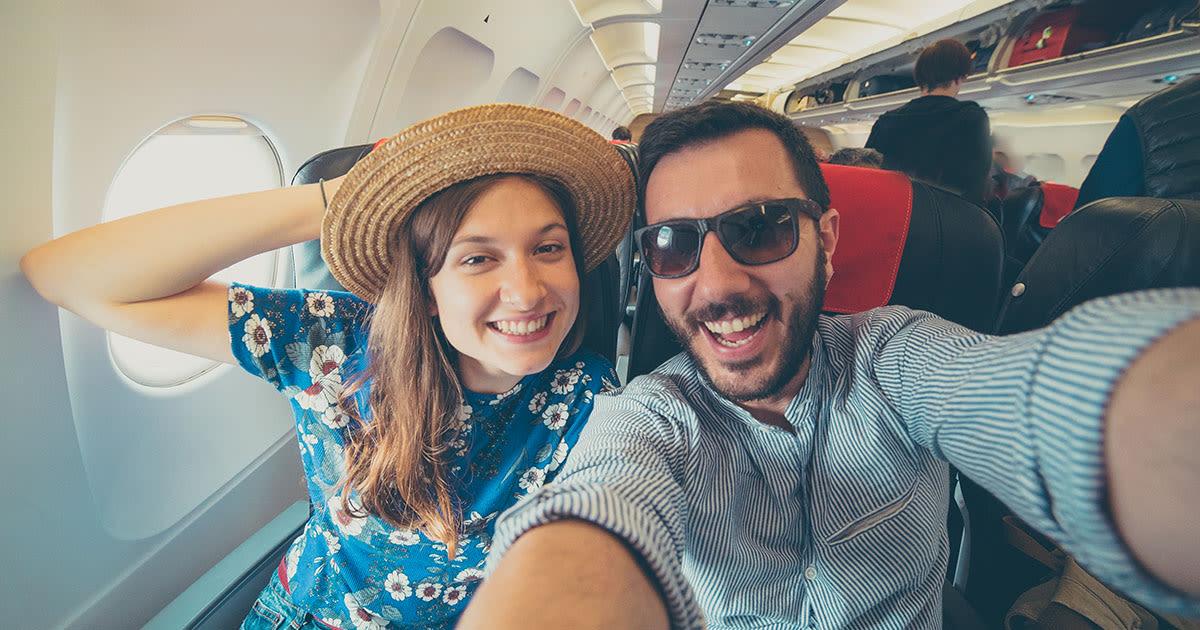 Junges Paar nimmt ein Selfie in einem Flugzeug