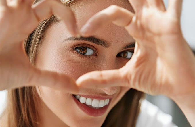 happy woman framing her eye with her fingers in a heart shape