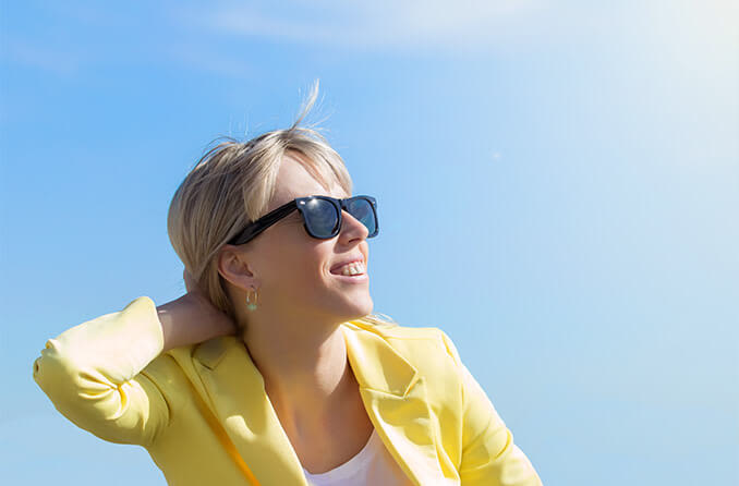 woman wearing Ray-ban sunglasses looking up at sun