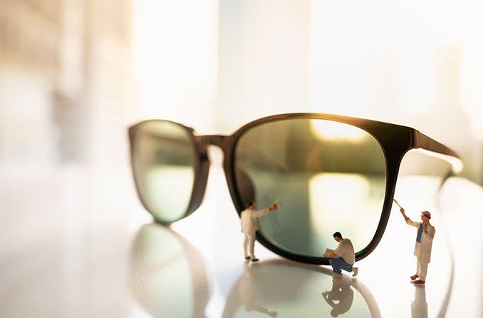 miniature men taking care of pair of sunglasses