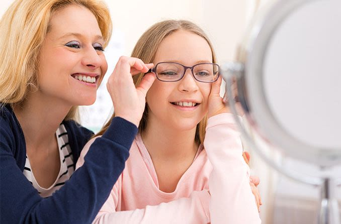 mother putting new pair of eyeglasses on daughter