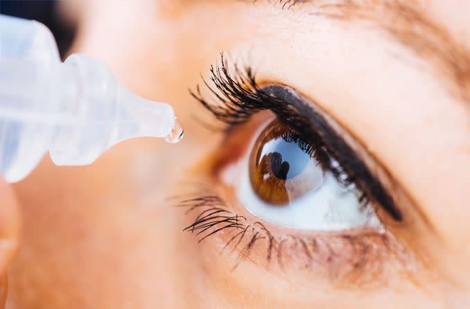 امرأة تضع قطرات العين