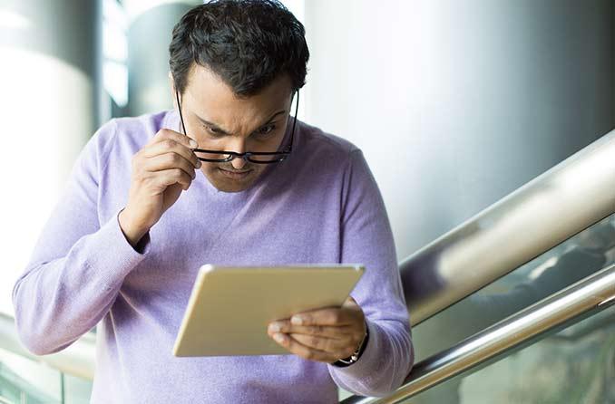 رجل يرتدي نظارة ينظر إلى شاشة الكمبيوتر اللوحي