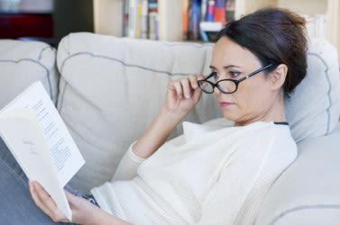 किताब पढ़ती हुई चश्मा पहने एक महिला