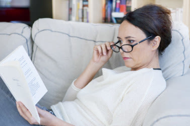 Woman with eye glasses reading a book